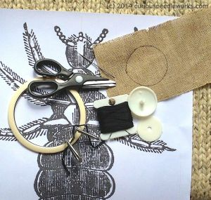 Parts list: Dritz craft fabric button, printout of a head louse, linen scrap, embroidery floss,  needle, scissors, and embroidery hoop.